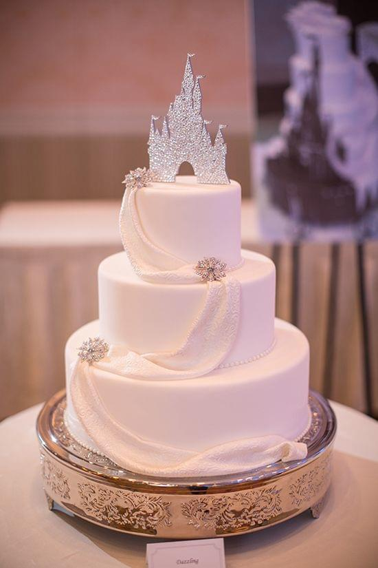 Elegant white cake with silver accents and castle topper for Disney wedding