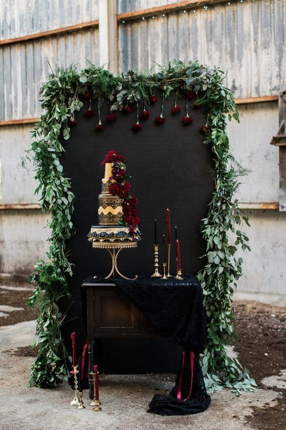 Moody wedding gold and burgundy cake against black background and greenery surrounded by candles