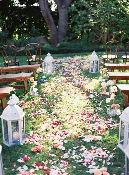 Garden colorful flower petals in aisle with lanterns