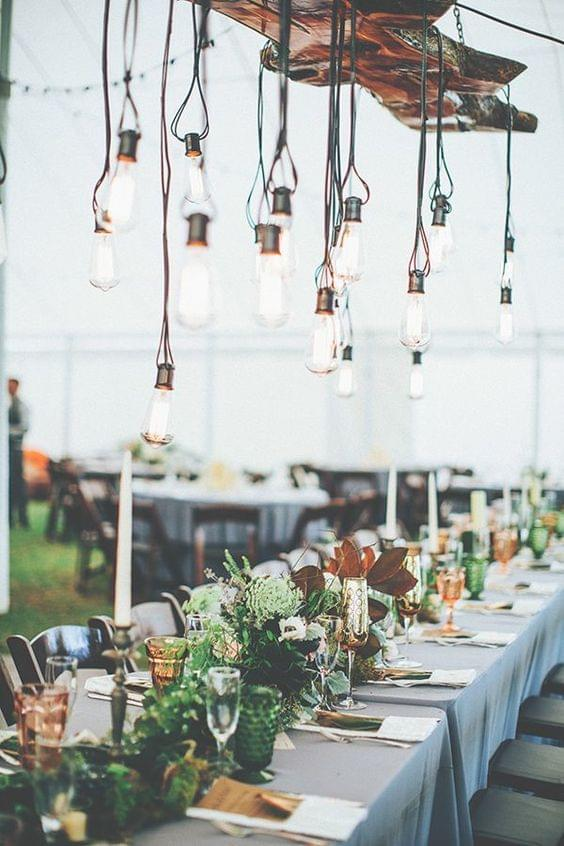 Industrial wedding with hanging lightbulbs and greenery centerpiece