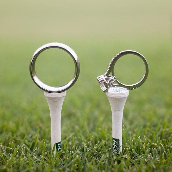 Preppy wedding photo of wedding rings on golf tees in grass