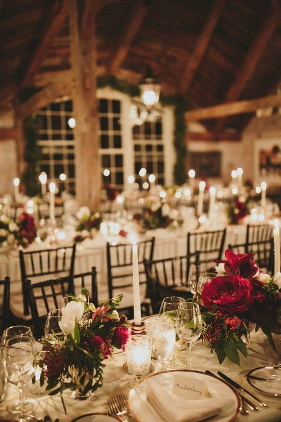 Comfy and cozy holiday wedding tablescape with red flowers and candles