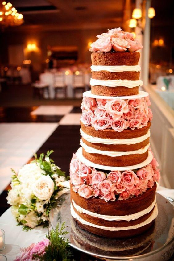 Naked wedding cake with white frosting and pink rose details