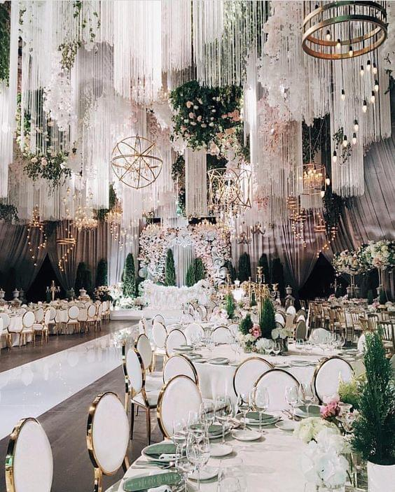 Glamorous white and gold tablescape with greenery and hanging lights