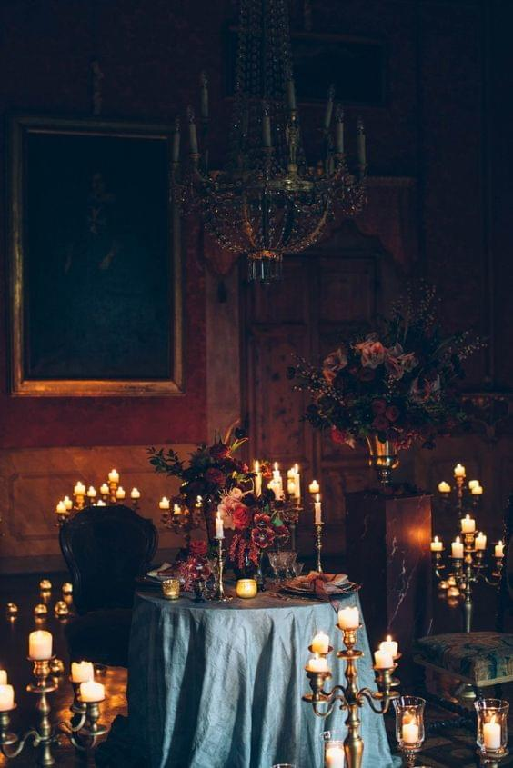 Moody wedding, dark atmosphere with chandelier and multiple candles surrounding with flowers