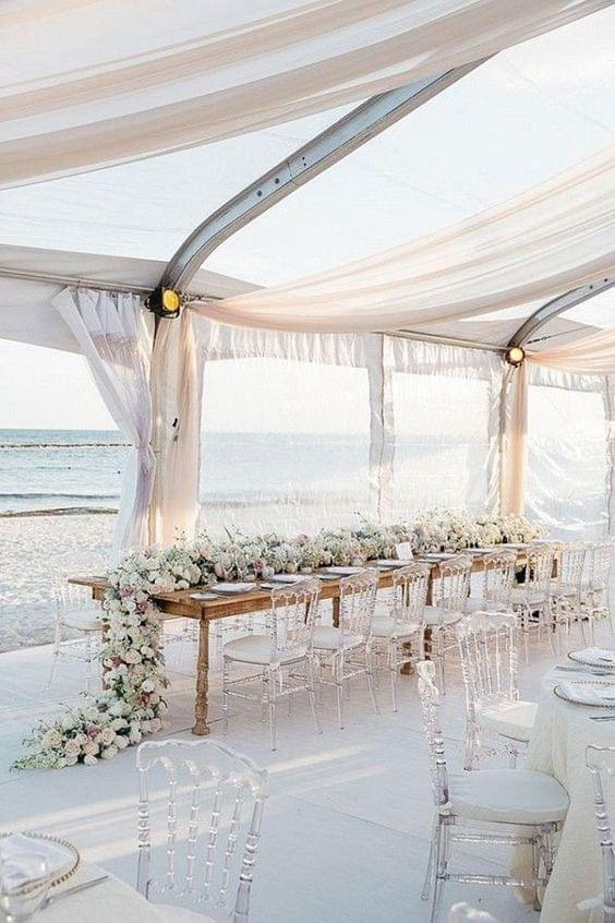 Beach wedding tablescape with flowing drapes and floral details