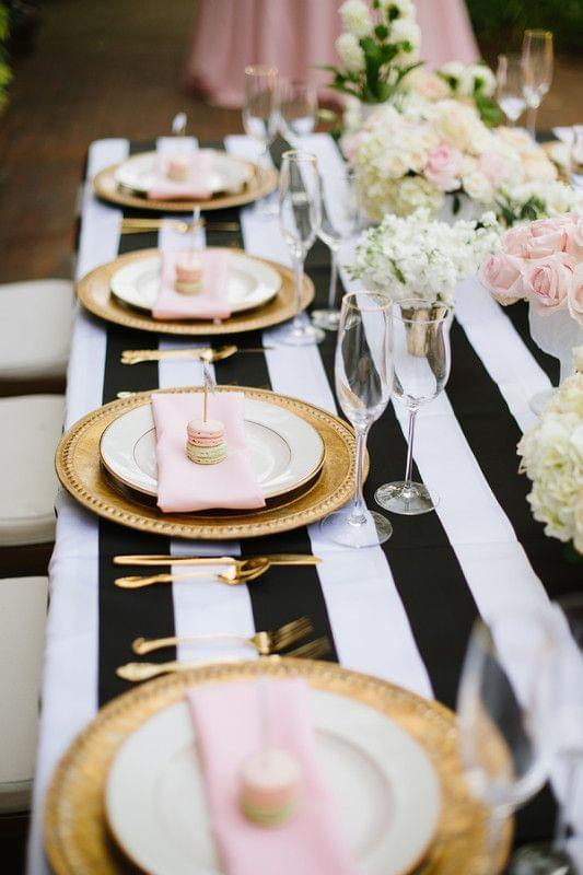 Preppy wedding tablescape with black and white striped table runner and pink and gold accents