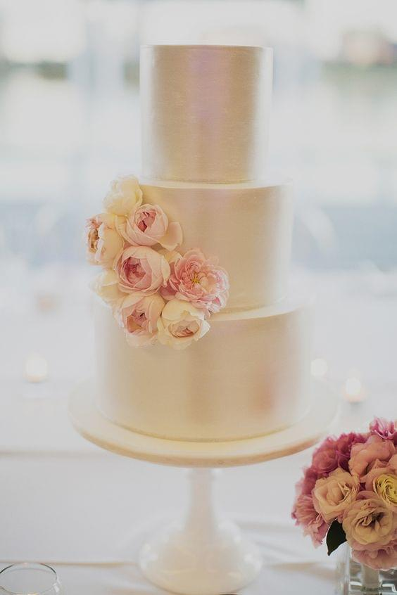 Simple and elegant wedding cake with shine and floral accents