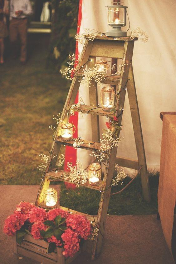 Rustic wooden ladder with candles and flowers