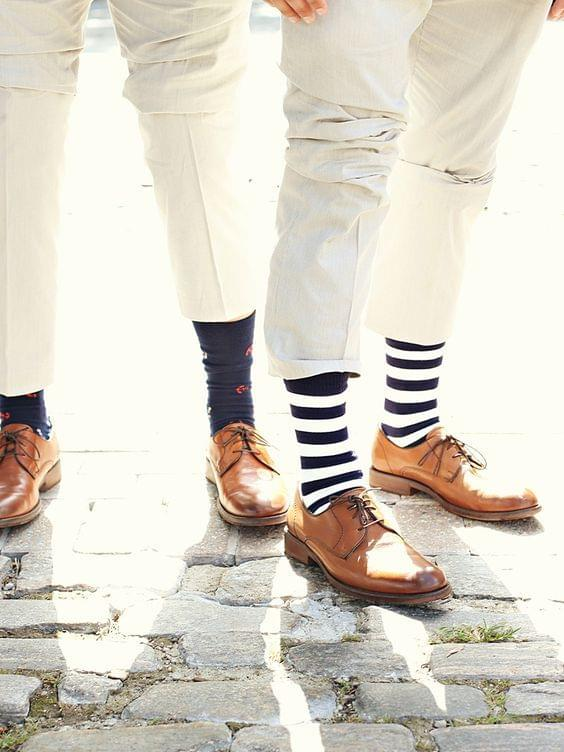Preppy wedding photo with groomsmen wearing fun patterned socks and brown shoes