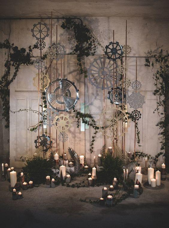 Industrial wedding gears background with greenery and lit candles on floor