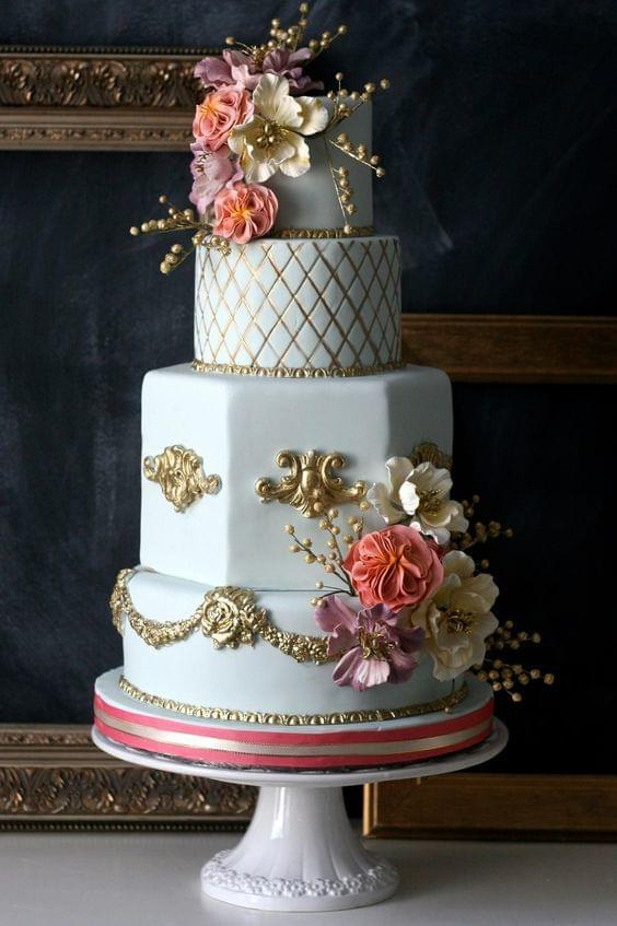 Glamorous light blue and gold wedding cake with floral accents