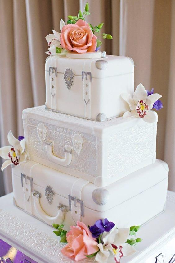 Travel themed stunning white and silver suitcase cake with floral accents