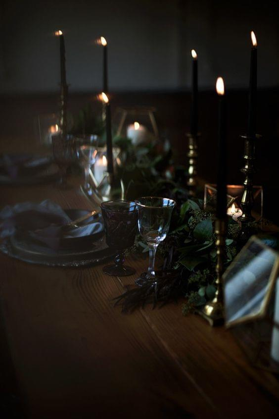 Moody wedding dark atmosphere with wooden table and lit candles