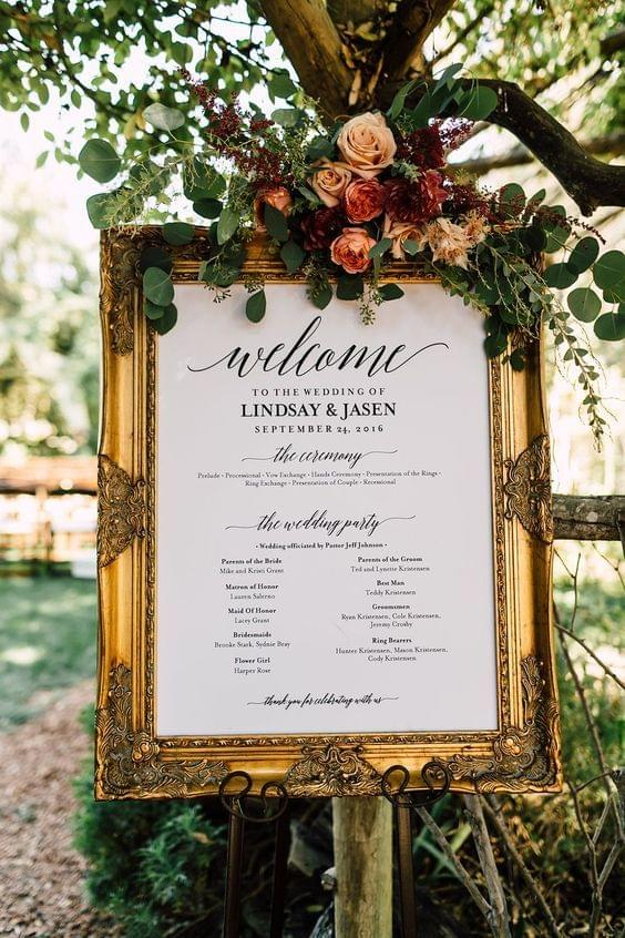 Garden wedding with elegant gold welcome sign with floral decor