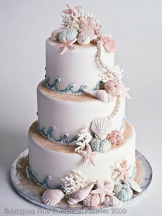 Beach wedding cake with seashells, pearls, and wave and sand details