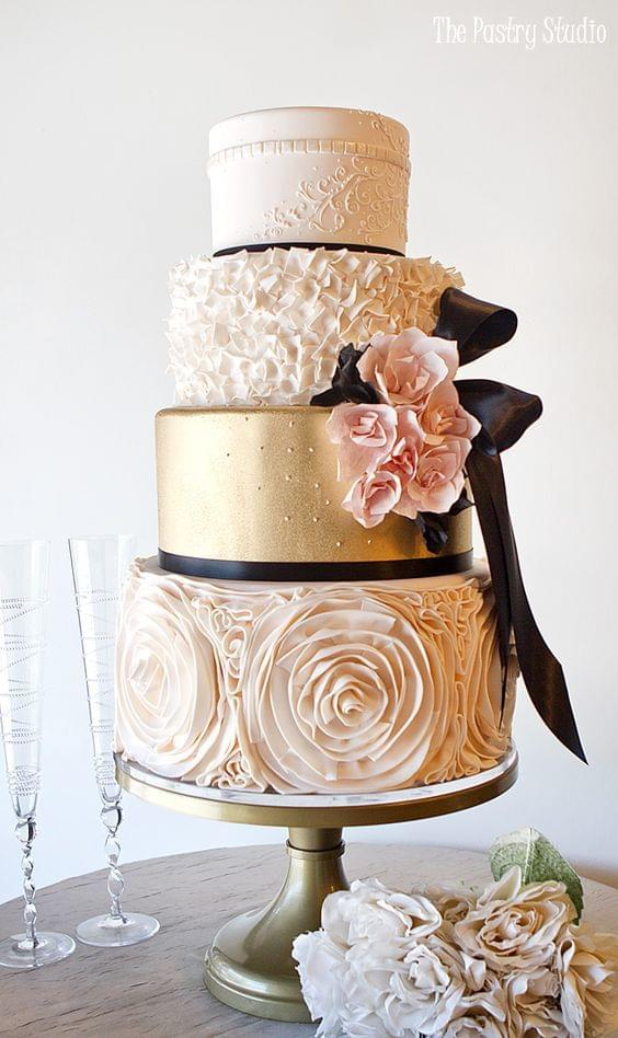 Glamorous light pink and gold wedding cake with big bow accent