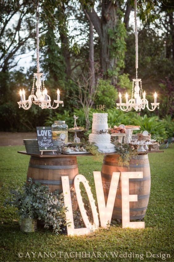 Summer wedding dessert table outside with hanging chandeliers